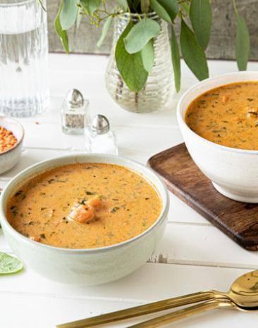 Orangene Curry-Suppe mit Süßkartoffel in zwei Schälchen