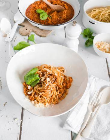 Spaghetti Bolognese auf weißem Teller garniert mit Basilikum.