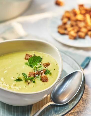 Zucchini-Kartoffel-Suppe in einem Teller mit Brotcroûtons garniert.